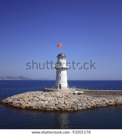 White beacon near coast with a red flag against the sea and the blue sky