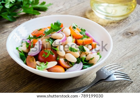 White Bean Salad with Cherry Tomatoes, Onion and Parsley on wooden background, copy space - healthy homemade organic vegetarian vegan diet protein salad meal food lunch