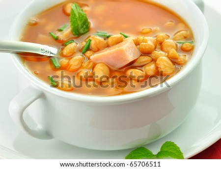 white bean soup with ham and tomatoes in a white soup cup