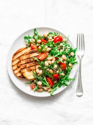 White beans, arugula, cherry tomatoes salad - delicious brunch, snack on a light background, top view