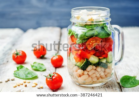 White beans cucumber tomato red pepper feta spinach salad in a jar. toning. selective focus #387246421