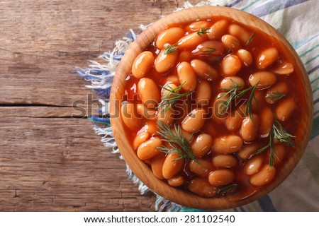 white beans in tomato sauce with dill in a wooden bowl closeup. horizontal view from above #281102540