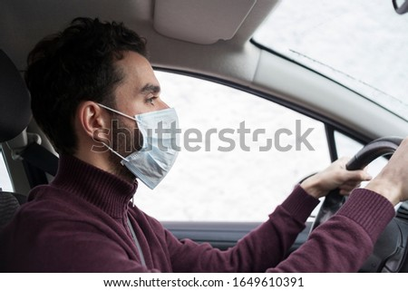 White bearded man driving on a car while wearing protective mask to avoid the infection of virus and polluted air spreading deseases. Health care, coronavirus, influenza and epidemics driving stills.