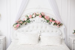 White beautiful bedhead decorated with flowers. Royal bedroom in white color