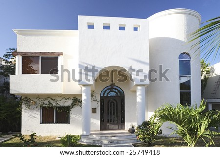 White beautiful house with exotic garden.