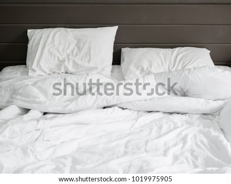 White Bedding Sheets And Pillow On Natural Stone Wall Room Background ,Unmade  Messy Bed After
