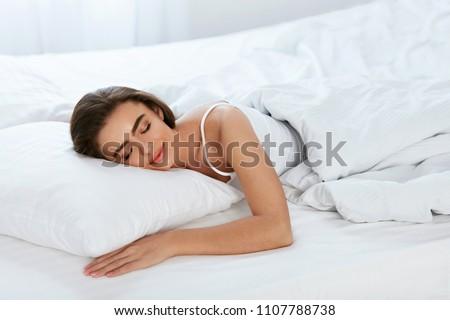 White Bedding. Woman Sleeping On Mattress With Pillow.