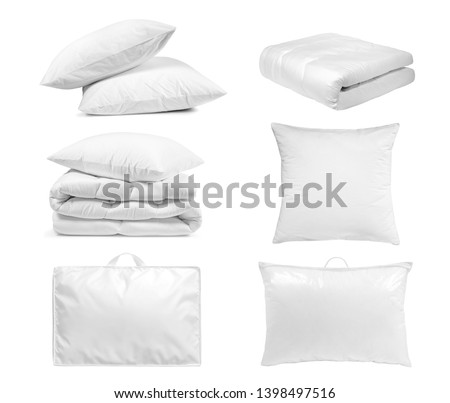 White bedroom textile items set isolated. Pillows and duvet- laying, folded, stacked and packed against the white background.