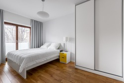 White bedroom with double bed and sliding door wardrobe