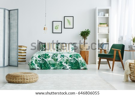 White bedroom with screen, bed, armchair, bookcase, lamp and pouf