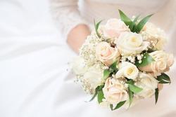 White, beige wedding bouquet. Bride, hands, arms