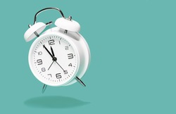 White bell alarm clock hovering over green background. 5 to 12 clock concept isolated. five to twelfe, time to act concept