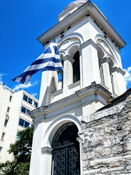 White bell tower with a Greek flag against a blue sky