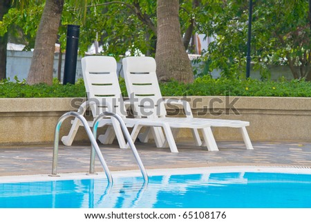 white benches beside swimming pool