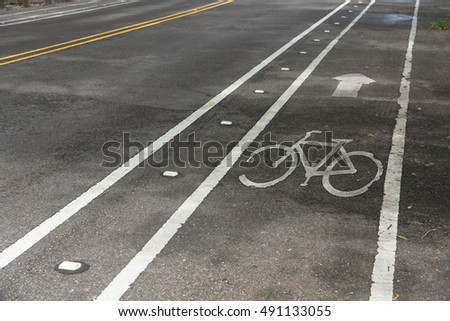 White bicycle sign on asphalt bike lane on city park. Concept background for Air Pollution Reduce and Cycling Health Benefits. #491133055