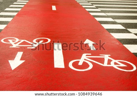 White bicycle sign with arrow on red asphalt, road sign bike in the street, bike path sign on the street, red blurred background