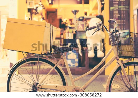 White bicycle with a yellow box in back seat parked in front of a cafe. Retro effect.