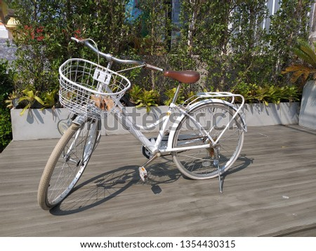 White bicycle with front basket and brown saddle on the wooden floor, bicycles are used for transportation, bicycle commuting, and utility cycling, recreational purposes #1354430315