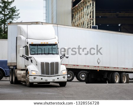 White big rig long haul semi truck with high cab and semi trailer turning on warehouse parking lot waiting for loading and possibility of continuing to the destination according to approved schedule
