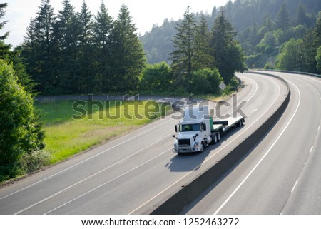 White big rig semi truck with hue roof spoiler transporting empty step down semi trailer for carry heavy-duty stuff driving on turning wide highway road with green trees to point of loading cargo #1252463272