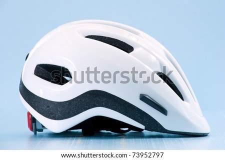 White bike helmet isolated on blue background. Lateral view.