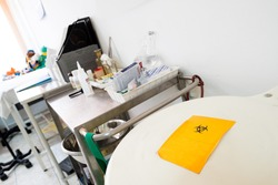White biohazard medical container with yellow hazard symbol filled with medical waste in a medical room.