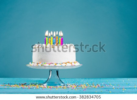 White birthday cake over blue background