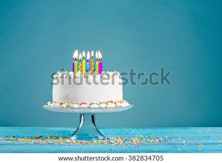 White birthday cake over blue background