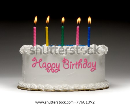 "White birthday cake profile on gradient background with five colorful lit candles and ""Happy Birthday"" written on the side with frosting"