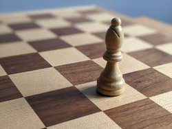 White Bishop chess piece isolated on a wooden chess board. Strategic placement and play. Rich brown and white checkered board. Mind using boarding games with tactics and skills.