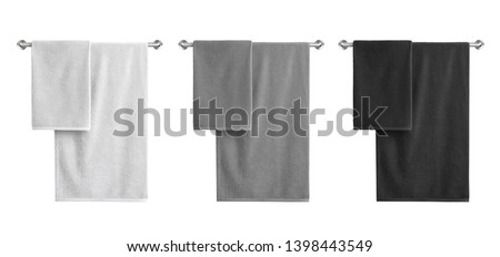 White, black and grey cotton terry towels hanging on a rail isolated