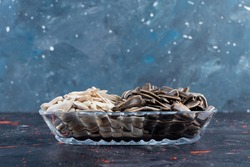 White-black sunflower seeds in glass plate, isolated over navy blue background. High quality photo
