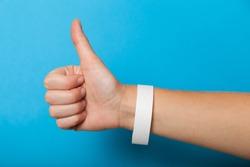 White blank bracelet on hand. Music festival branding wristband, adhesive paper accessory for concert, event. mockup.