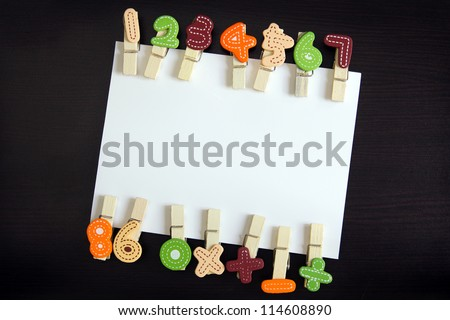 White blank card surrounded by clothespin in black wooden background