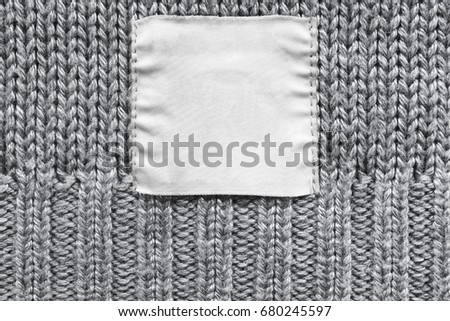 White blank clothes label on gray knitted background closeup