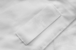 White blank clothes label on white linen as a background