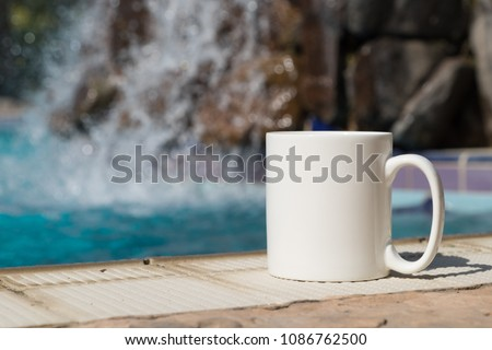 White blank coffee mug mock up, set on the poolside with a waterfall in the background.\tPerfect for businesses selling mugs, just overlay your quote or design on to the image.