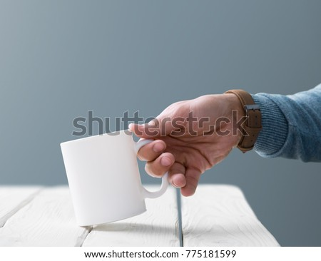 White blank cup mock-up in man's hand over table