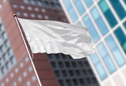 White blank flag waving in the wind against blurred modern building. Perfect mockup to add any logo, symbol or sign
