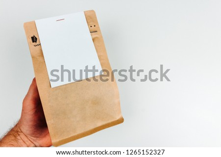White blank label on blank packaging been held to the left of the frame.