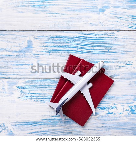 White blank model of passenger plane and passports on blue wooden background  #563052355