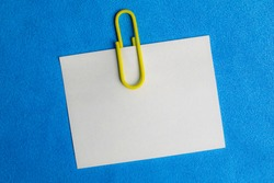 white blank note pinned to a blue notice board with a paper clip.