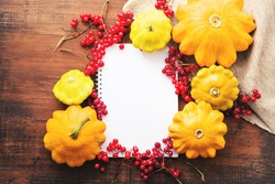 White blank notebook for your text and yellow squash with viburnum berries on an old wooden surface, top view.  Thanksgiving background