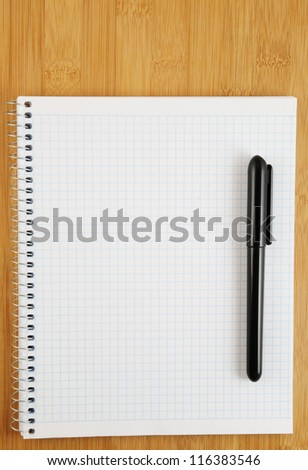 White blank notebook with pen on wooden background