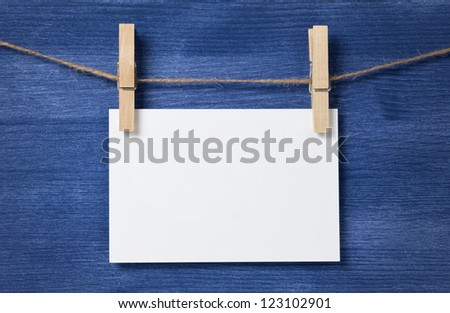 white blank paper card hanging over wood background, template