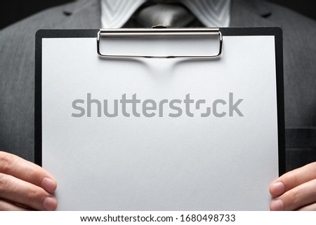 white blank paper sheet closeup in businessman hand, gray suit, dark wall background, blank space for text 商業照片 ©