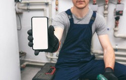 White blank screen mobile phone in plumber's hand in protection gloves