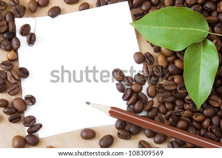 White blank with coffee beans, green fresh leaves and pencil on wooden table