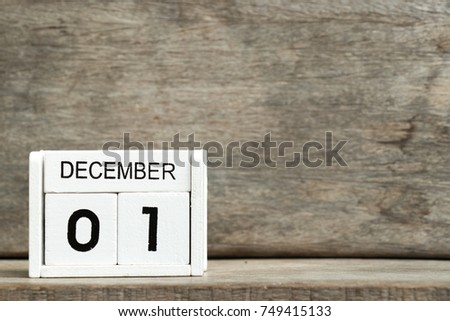 White block calendar present date 1 and month December on wood background