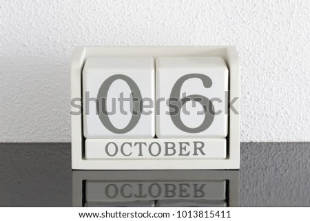 White block calendar present date 6 and month October on white wall background #1013815411